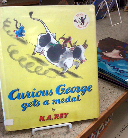Curious George gets a medal, on a cow!