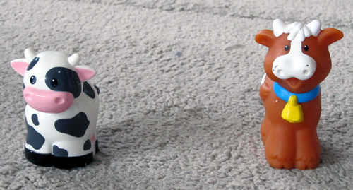 Toy cows sitting on a rug