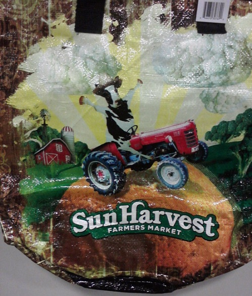 Henry's Marketplace reusable shopping bag with cow driving a tractor