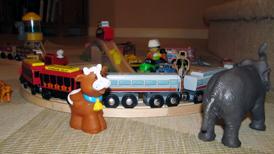 Toy train set with animals and a cow